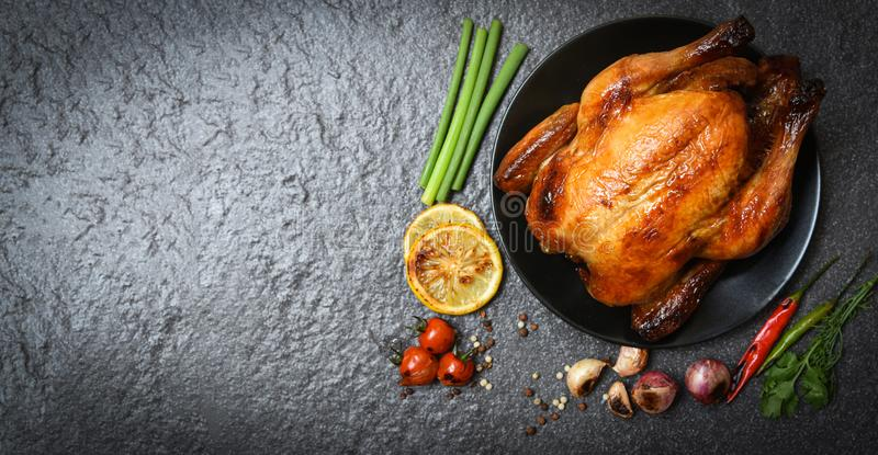 烤鸡/被烘烤的整鸡烤用草本和香料和黑暗的背景 库存照片