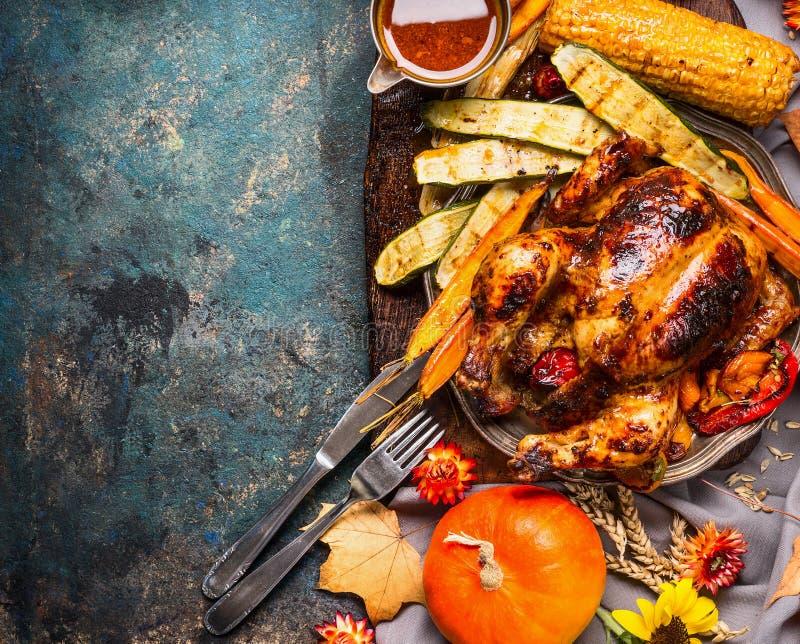 烤整个火鸡用南瓜、菜和调味汁为感恩天在黑暗的土气背景 免版税库存图片