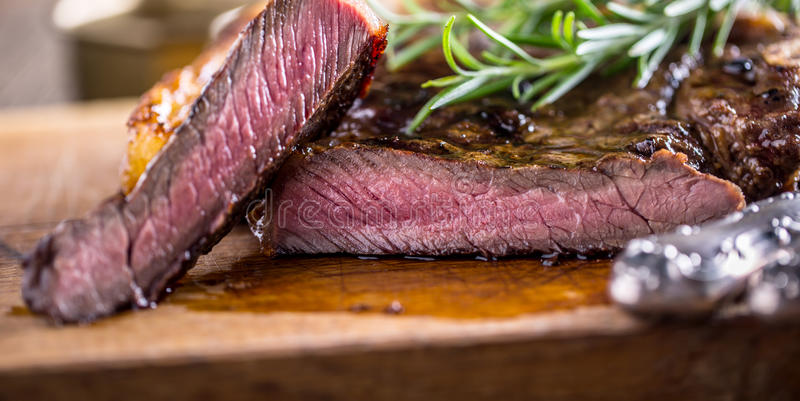 烤水多的牛肉丁骨牛排用盐胡椒和迷迭香 图库摄影
