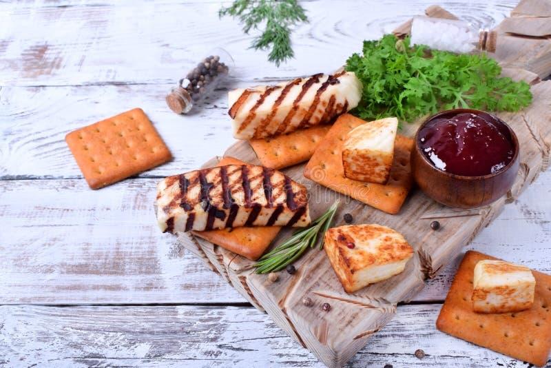 烤adyghe乳酪、薄脆饼干、红色果酱、香料和水芹沙拉在木板 免版税库存图片