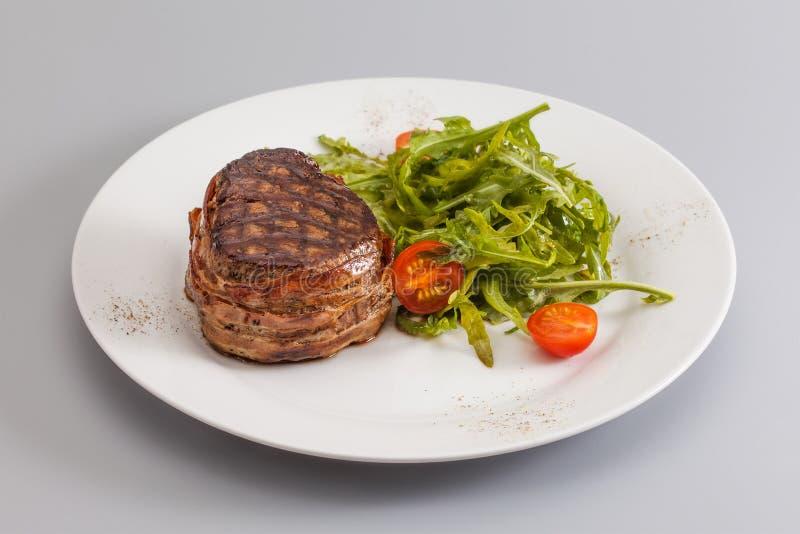 烤bbq牛排包裹了烟肉,蔬菜沙拉用在白色板材,灰色背景的西红柿 免版税图库摄影