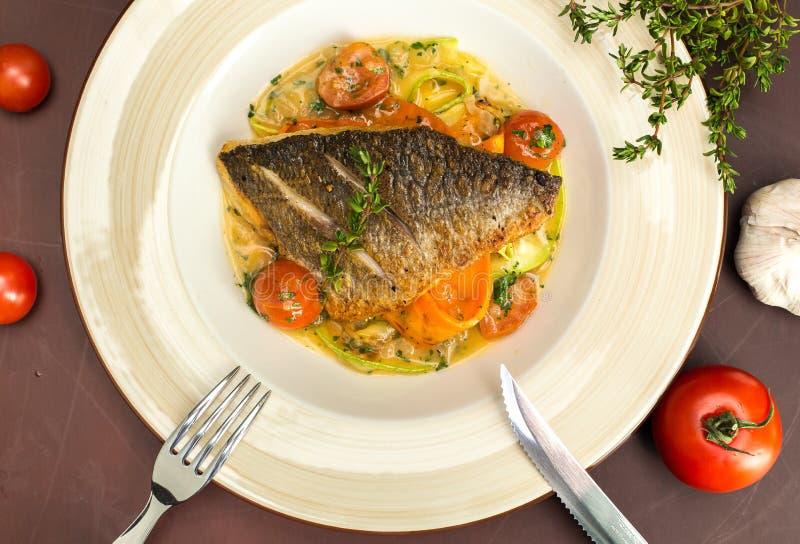 烤dorado鱼用油煎的土豆、柠檬和蕃茄 免版税库存照片
