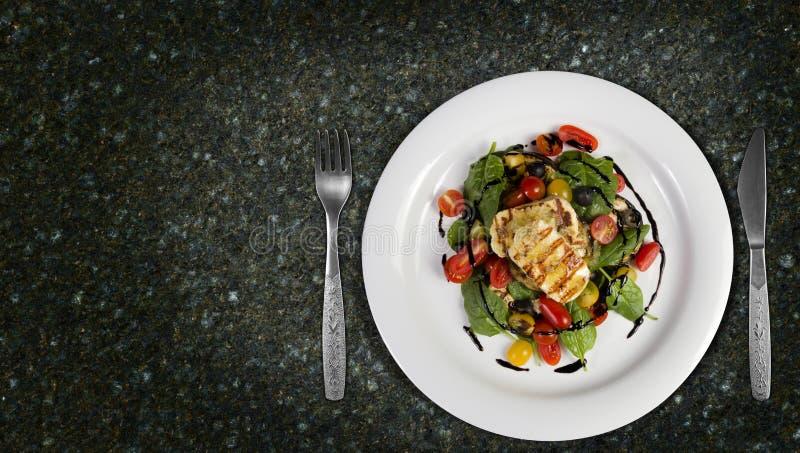 烤Halloumi乳酪倒与大蒜橄榄油沙拉巫婆烤了茄子、西红柿、黑橄榄和菠菜 图库摄影