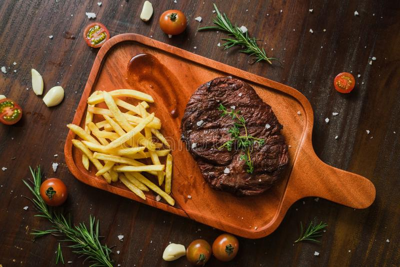 烤kebab烤了肉与法国frieson的牛排谎言切砧板辣椒,与t的土气老典雅的木利器 免版税库存照片