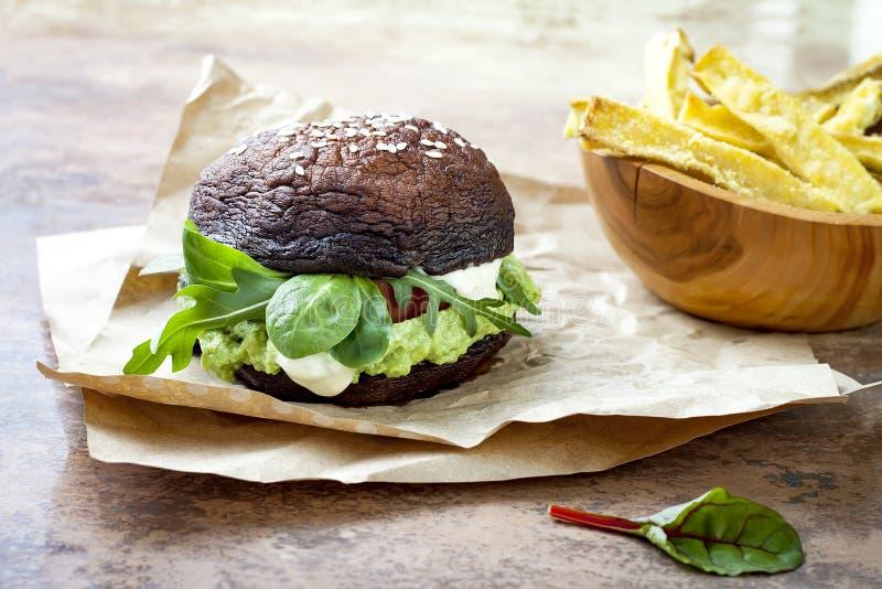 烤portobello小圆面包蘑菇汉堡 素食主义者,面筋释放,自由的五谷,与鳄梨调味酱捣碎的鳄梨酱,新鲜蔬菜的健康素食者汉堡包 免版税库存照片