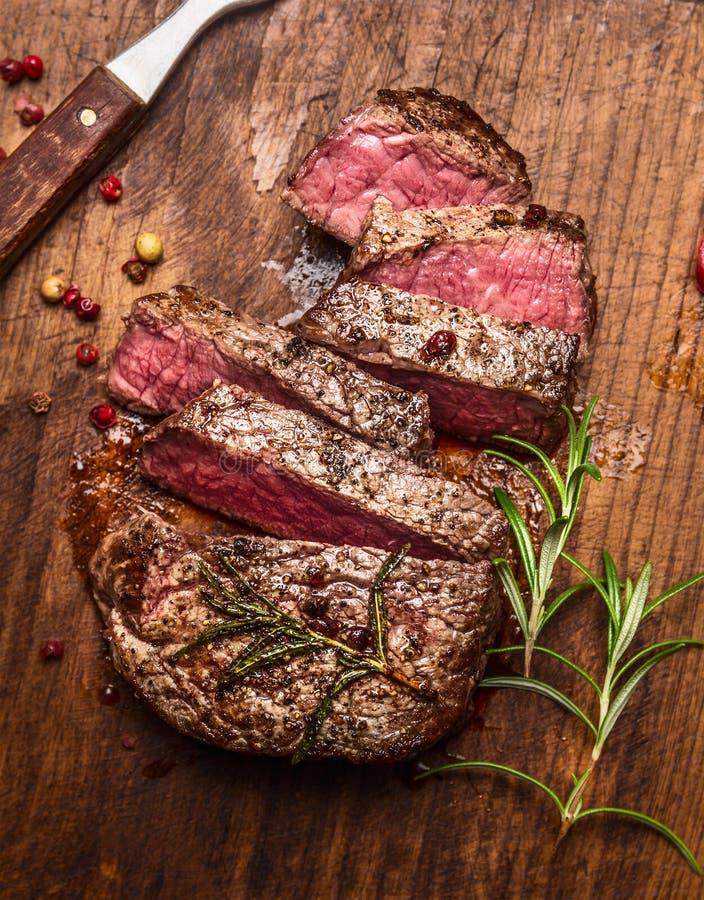 烤ribeye牛排切了†‹在一个切板的†‹有叉子、迷迭香和胡椒的,顶视图,关闭 库存照片