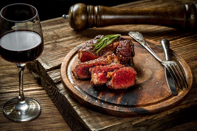 烤ribeye牛排用红葡萄酒、草本和香料在木桌上 免版税库存图片