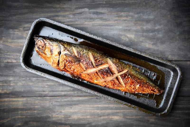 烤saba鱼用在盘子的甜调味汁有黑暗的背景 免版税库存图片