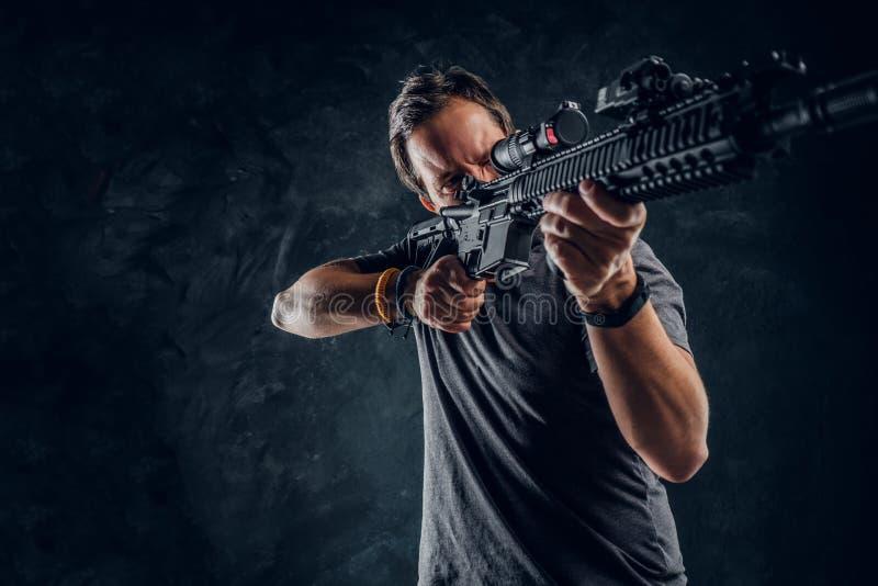 烦乱中年人在拿着攻击步枪的便服穿戴了并且瞄准目标 工作室照片 免版税图库摄影