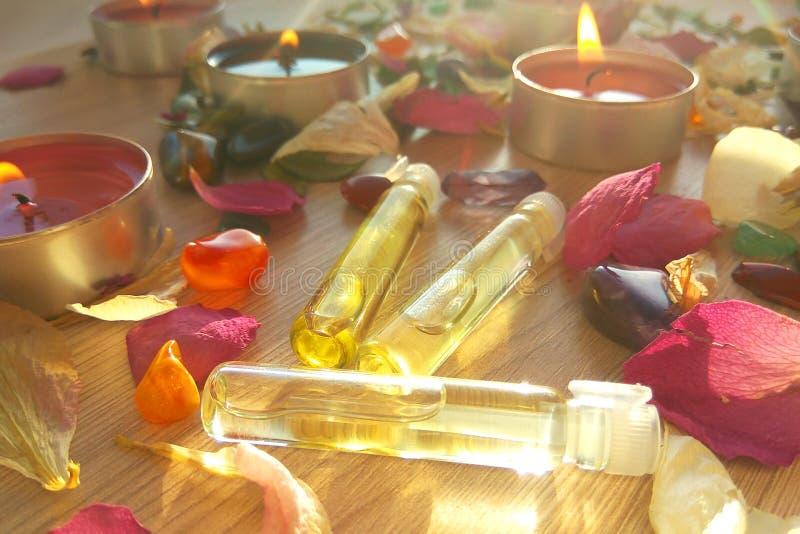 烧与根本温泉油的蜡烛,上升了花瓣和五颜六色的宝石在木背景 库存图片