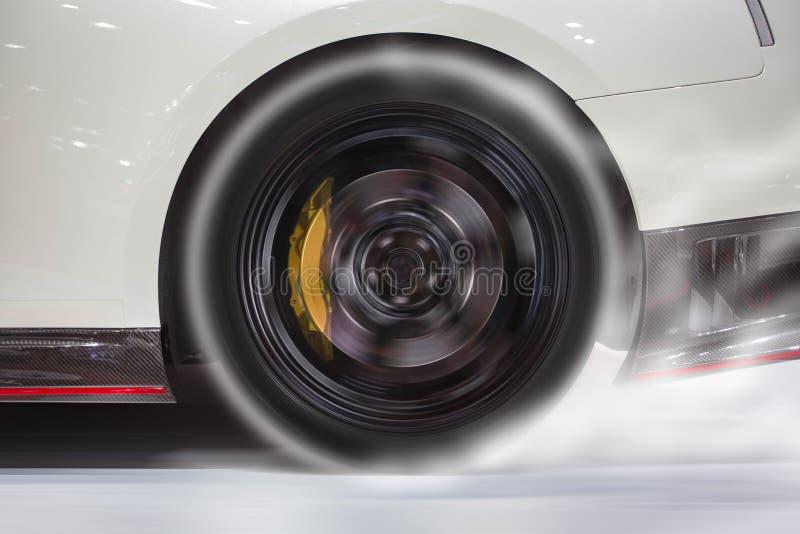 烧后轮轮胎的跑车在开始前加热好牵引的橡胶赛跑 免版税库存图片