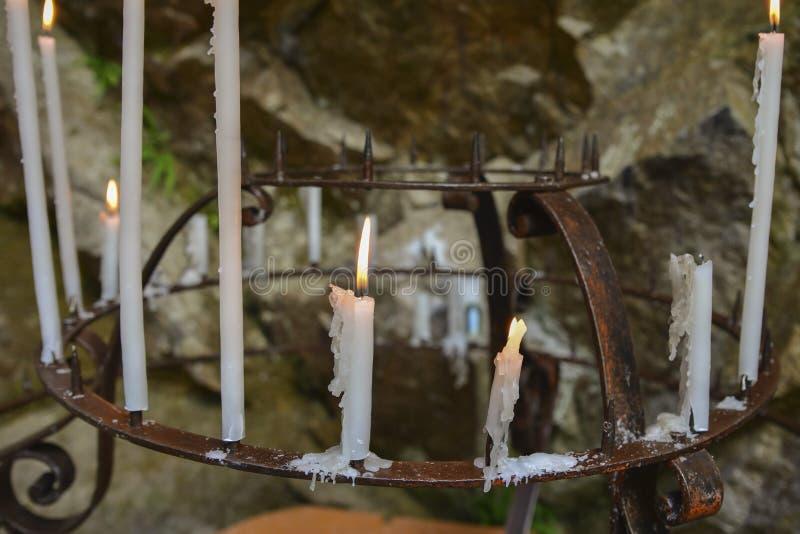 烧在卢尔德洞穴的许多蜡烛  免版税库存图片