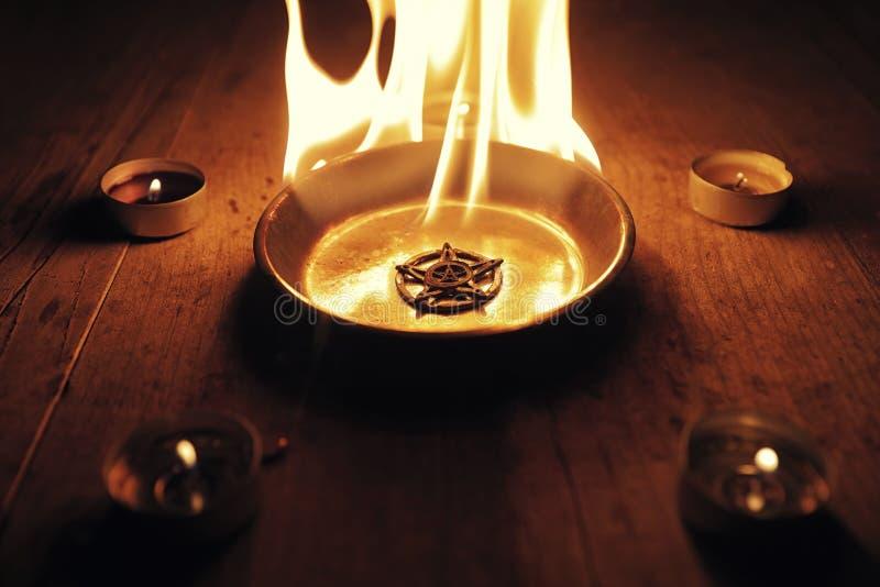 烧在火焰的老五角星形 免版税库存图片
