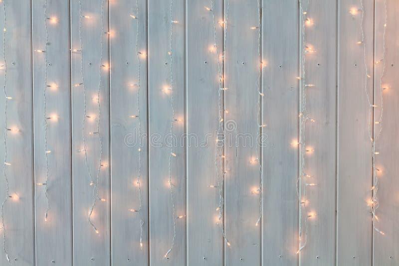 烧在白色木背景的圣诞灯 新年后面 库存照片