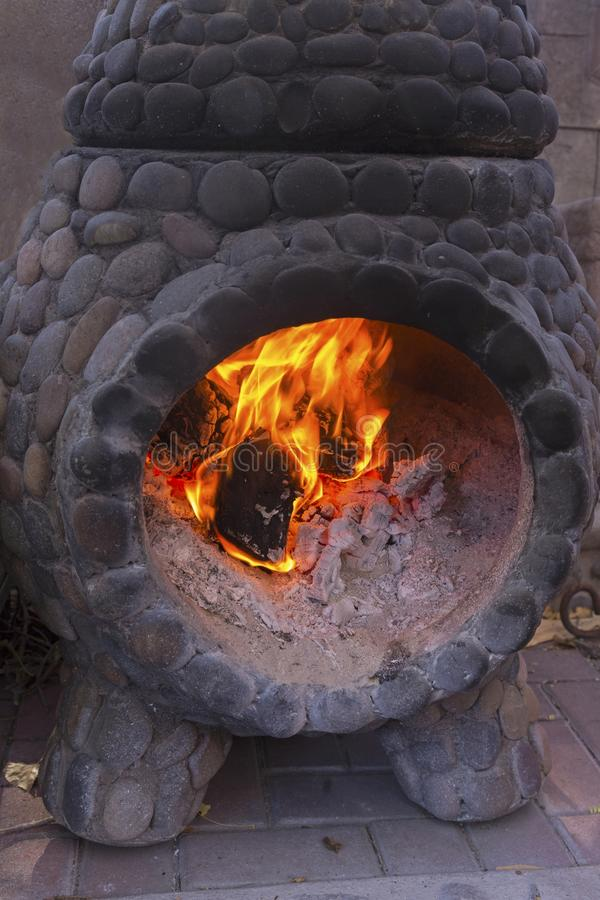 烧在老木炭石壁炉的火 免版税库存图片