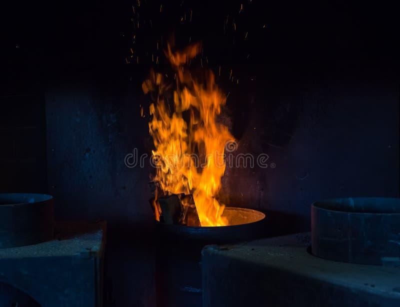 烧在金属的火焰滚磨,并且传播发火花 库存图片