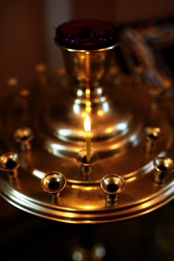 烧在金黄烛台的蜡烛在教会里 免版税库存图片