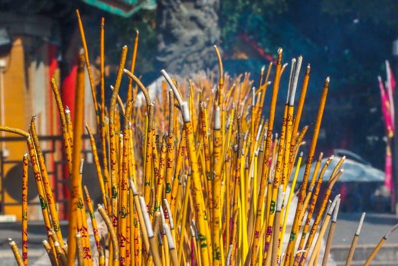 烧在香炉在宝莲寺,大屿山,香港的黄色佛教祷告棍子 库存图片
