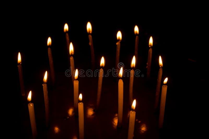 烧在黑背景的晚上的许多圣诞节蜡烛 免版税图库摄影
