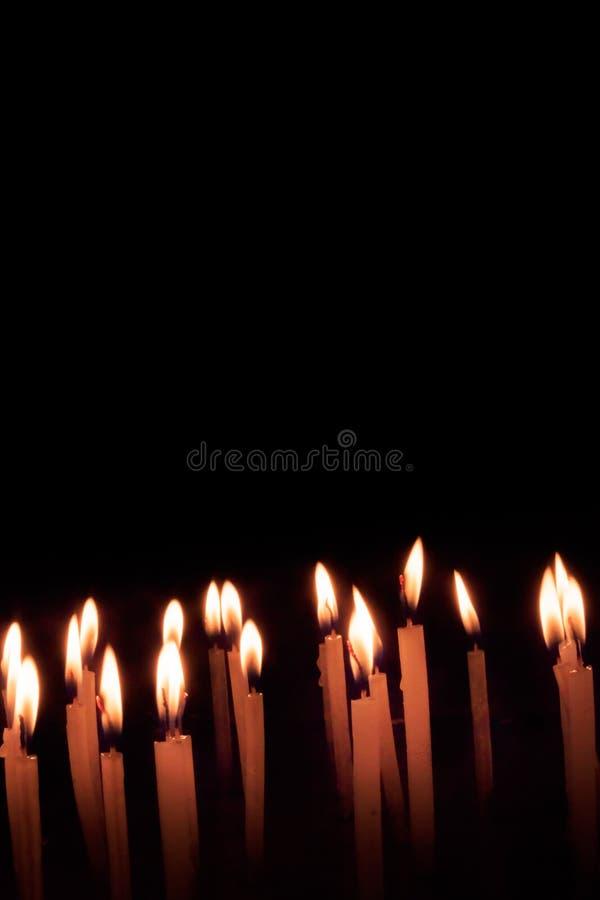 烧在黑背景的晚上的许多圣诞节蜡烛 免版税库存照片