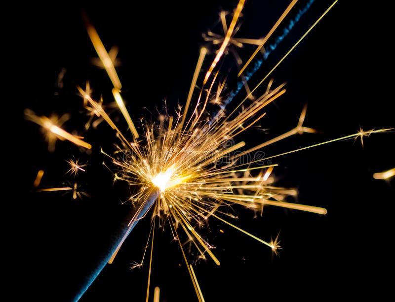 烧在黑背景,祝贺问候党新年好,圣诞节庆祝的烟花闪烁发光物 库存照片