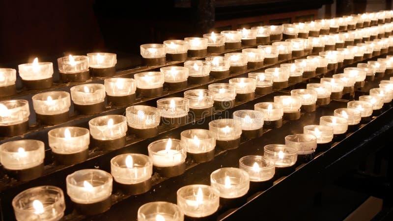 烧被点燃的蜡烛/tealights行在宽容基督教会里 库存照片