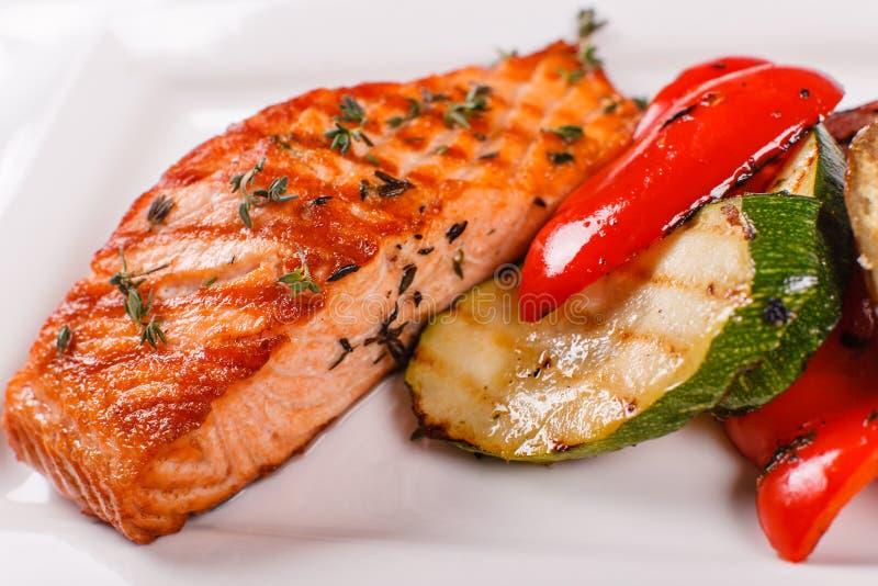 热和辣内圆角红色鱼 烤牛排三文鱼或鳟鱼用格栅辣椒粉和夏南瓜 健康食物,海鲜和 库存图片