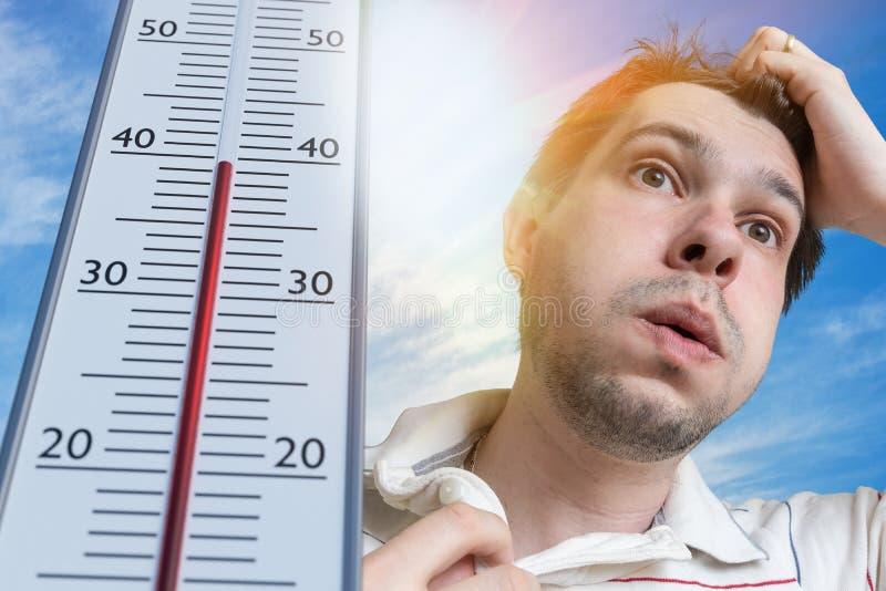 热天气概念 年轻人冒汗 温度计显示高温 太阳在背景中 免版税库存照片