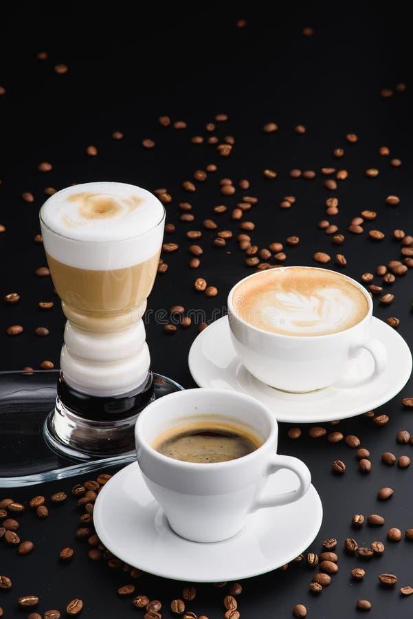 热奶咖啡、Americano和拿铁在一张照片在黑背景 免版税图库摄影
