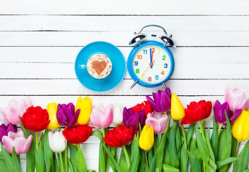 热奶咖啡和时钟在花附近 库存照片
