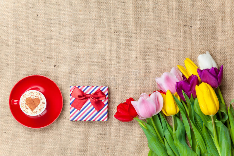 热奶咖啡和礼物盒在花附近 免版税库存图片