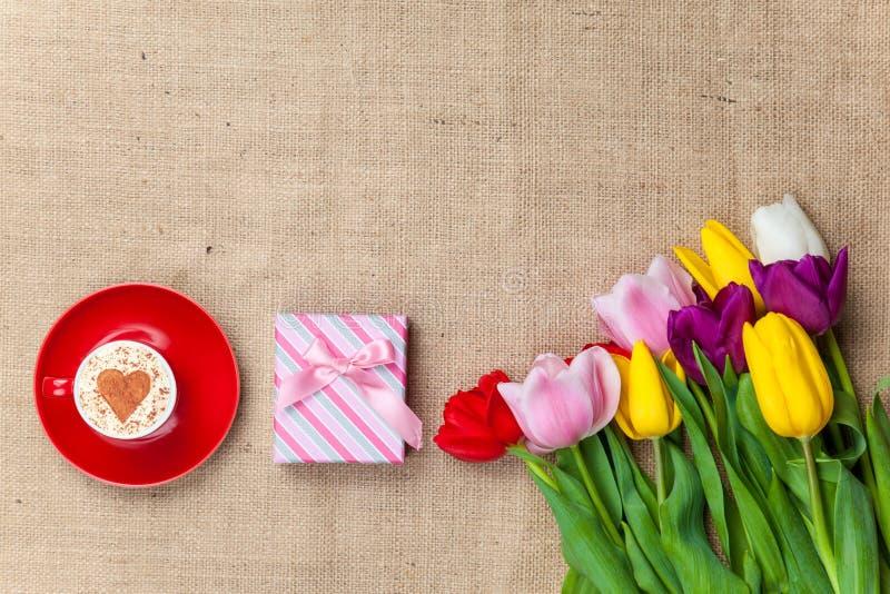 热奶咖啡和礼物盒在花附近 库存照片