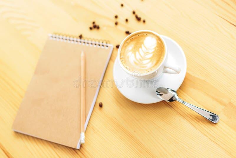 热奶咖啡和笔记本在木桌上 库存照片