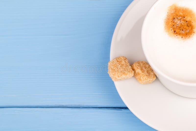热奶咖啡和蔗糖在一张蓝色桌上 免版税库存照片