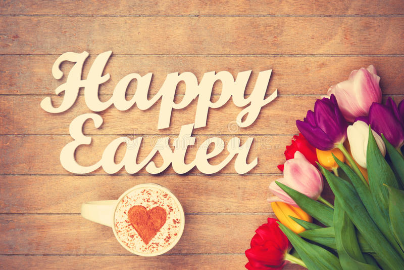 热奶咖啡和词在花附近的复活节快乐 库存图片