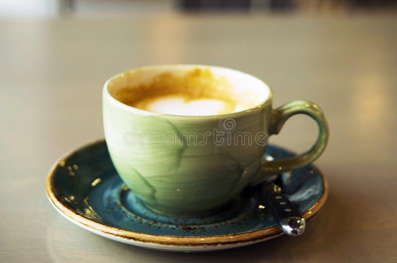 热奶咖啡或拿铁艺术咖啡由牛奶做了在桌在咖啡馆 r 库存照片