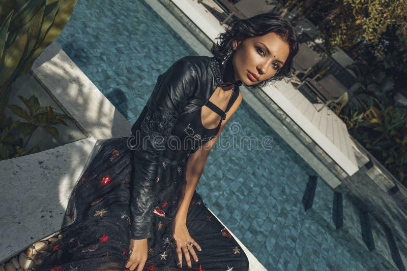 热带别墅的美丽的年轻时髦的妇女在游泳po附近 免版税库存图片
