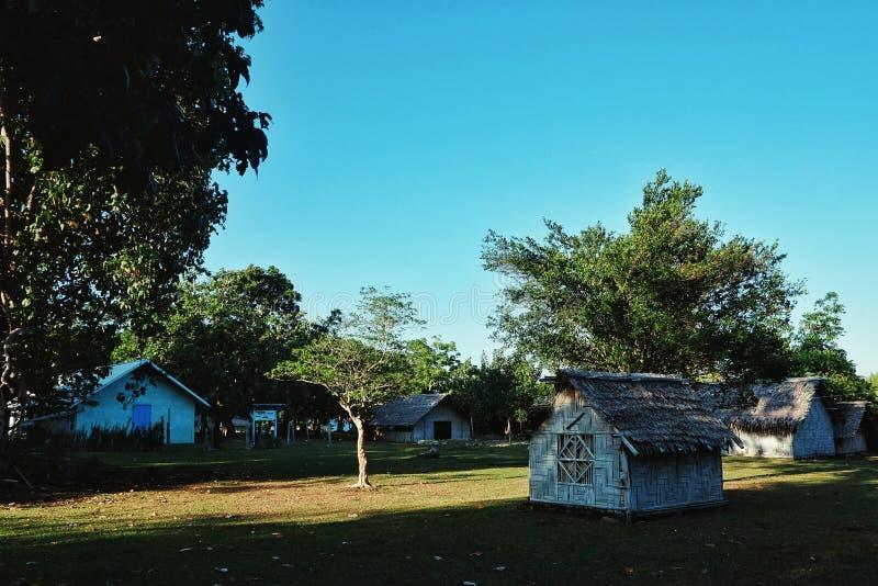 热带南太平洋的小被隔绝的遥远的村庄有竹和棕榈叶小屋和好的高大的树木的在日落 库存照片