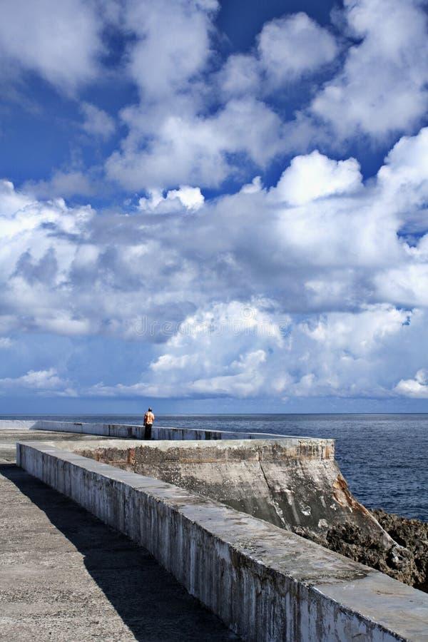 热带城市沿海岸区的孤独的人  免版税库存图片