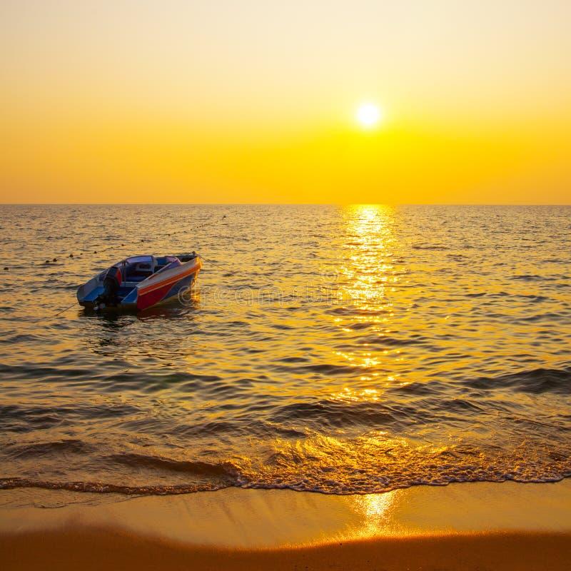 热带手段海滩和小船在日落的海 免版税库存照片