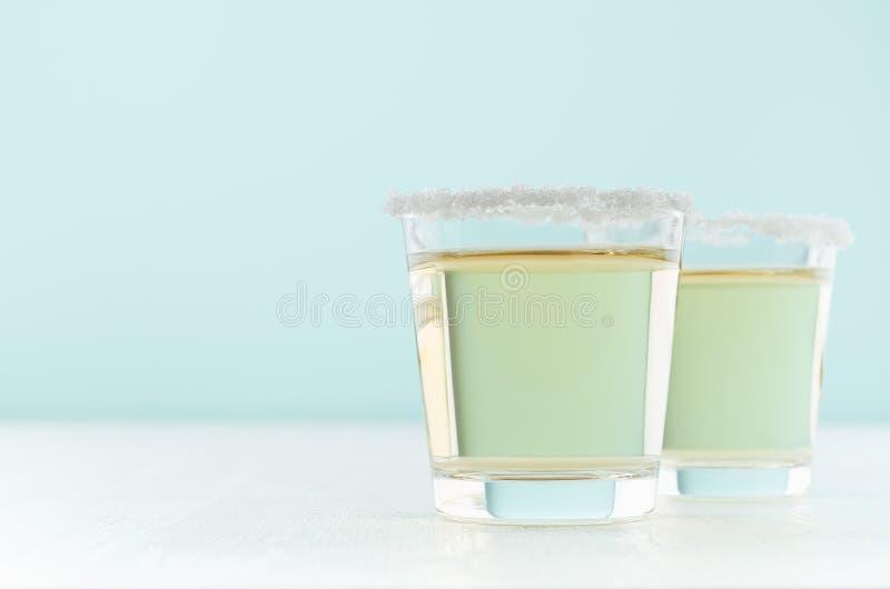 热带新鲜的酒精黄色饮料-在两个小玻璃的金黄龙舌兰酒与盐外缘在典雅的淡色绿色厨房里 免版税库存照片