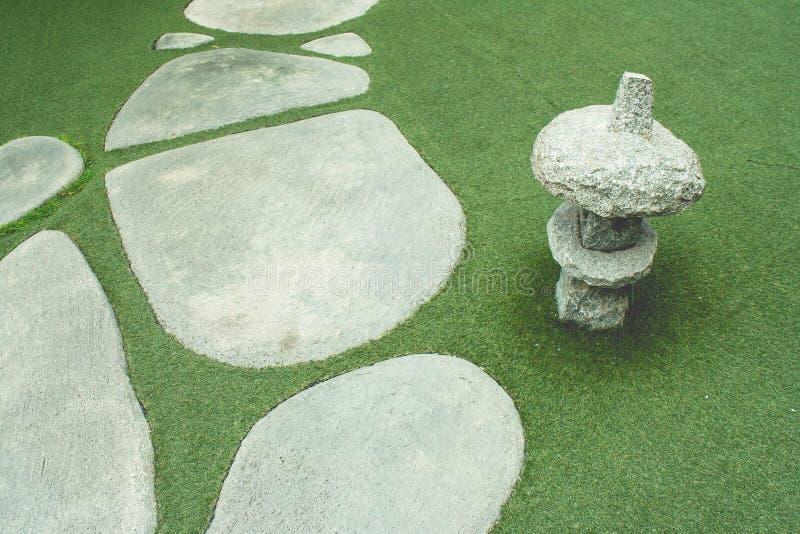热带日本室外庭院:小径或走道在绿草草甸领域旁边 免版税库存照片