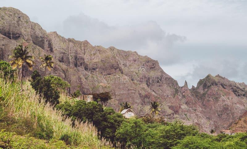 热带植被围拢的地方石住宅 上升在背景的锋利的山形成 圣安唐岛 图库摄影