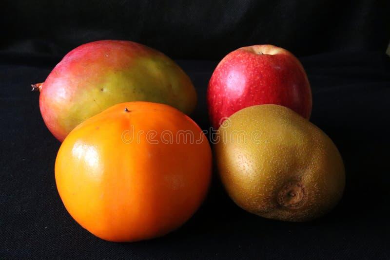 热带水果特写镜头,芒果,苹果计算机,猕猴桃,反对黑背景的柿子 库存照片