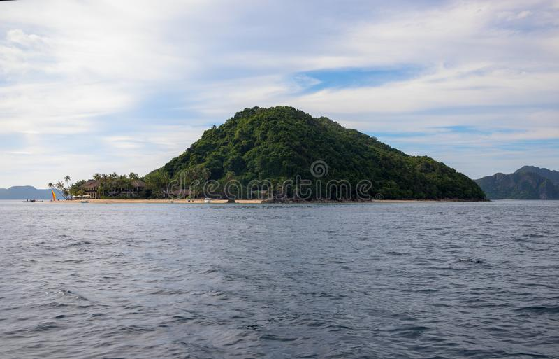 热带海岛在寂静的海 巴拉旺岛海岛海景 菲律宾旅行照片 有沙滩的美丽的绿色海岛 图库摄影