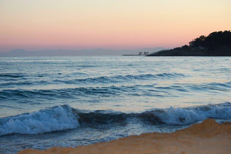 热带海滩日落风景  波浪,山,棕榈树 库存照片