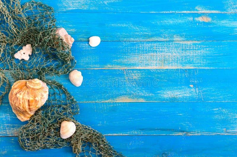 热带海背景 不同的壳,在蓝色委员会的老鱼网,顶视图 题字的自由空间 r 免版税库存照片