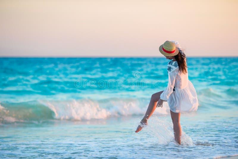 热带海滩的年轻美丽的妇女在日落 后面观点的女孩在美好的礼服背景中海 免版税库存照片
