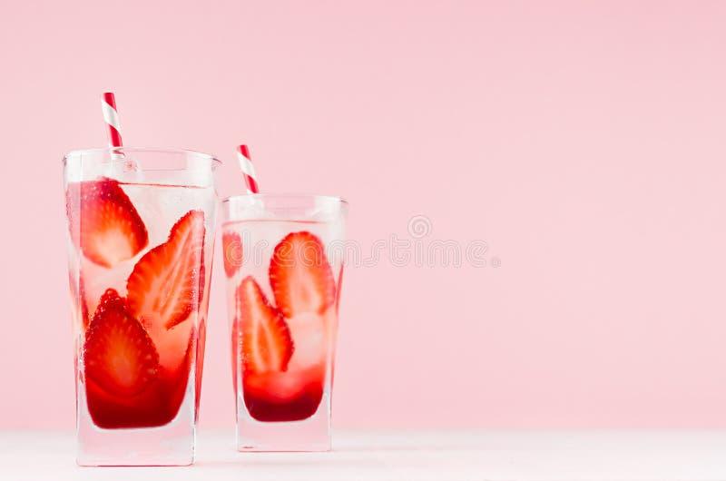 热带清凉醇草莓饮料,苏打水、冰块、草杆、优雅的粉色背景和白木板 免版税库存图片