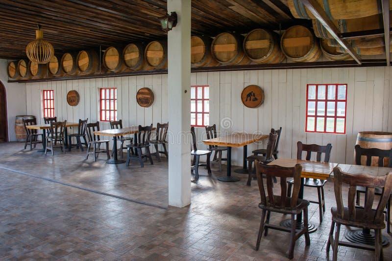 热带看法在餐馆,许多与葡萄酒桶的小组木桌和椅子在屋子里装饰 免版税库存图片
